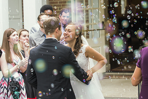 Wedding photograph of newlyweds leaving the church with bubbles