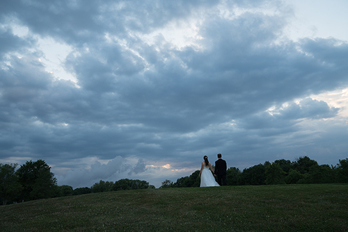 Dramatic wedding photograph of a bride and groom walking through