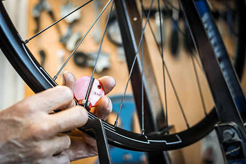 Abstract photo of a bicycle mechanic working on bike spokes