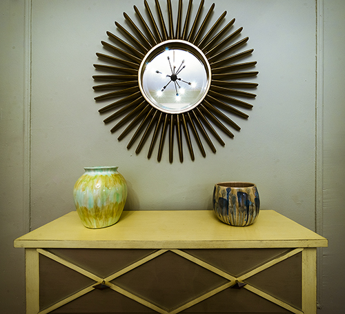 Photo of an abstract wall clock hung above a dresser